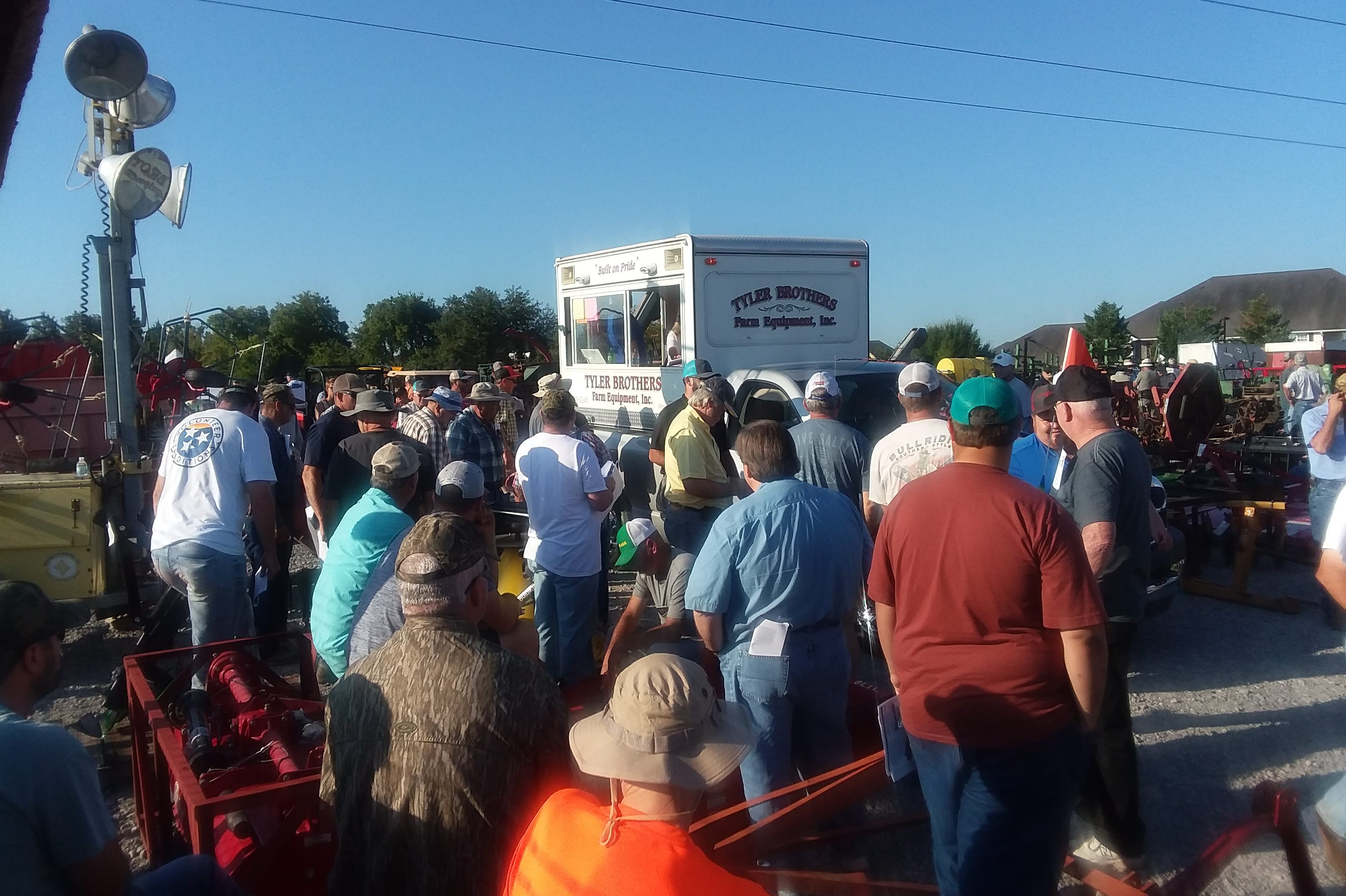 Two auctioneers travel around the 4 acre lot filled with new and used farm equipment, followed by hundreds of bidders.